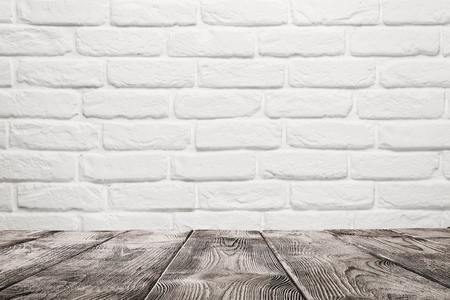 Empty wooden table over white brick wall background with copy space
