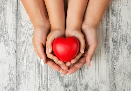 Love, family concept. Close up of mother and children hands holding red rubber heart together Standard-Bild