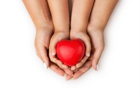 Liebe, Familienkonzept. Nahaufnahme von Mutter und Kinder Hände halten rote Gummi Herz zusammen isoliert auf weißem Hintergrund Standard-Bild