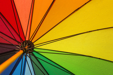Autumn background, close up of colorful umbrella in the rain with copy space