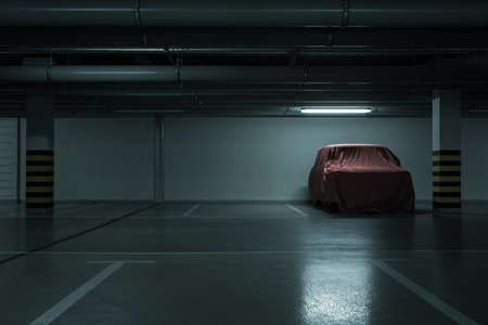 Red covered vintage car in empty underground parking background with copy space Foto de archivo