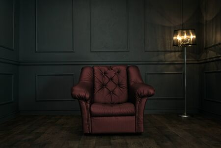 Leerer roter Lehnsessel im eleganten dunklen Raum mit Kopienraum Standard-Bild