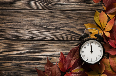 Time for autumn concept, close up of clock on wooden background with copy space Standard-Bild
