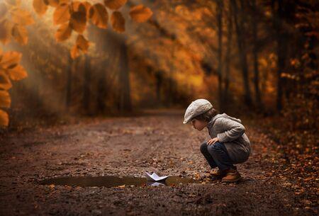 Kleiner Junge, der mit dem Papierboot in der Herbstwaldpfütze spielt