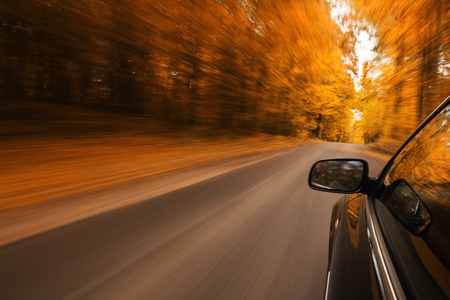 Close up of a sports car speeding on the empty, autumn road with copy space
