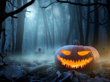 Halloween-Hintergrund, Abschluss oben des Kürbislaternenkürbises Jacks im gespenstischen Wald nachts mit Kopienraum