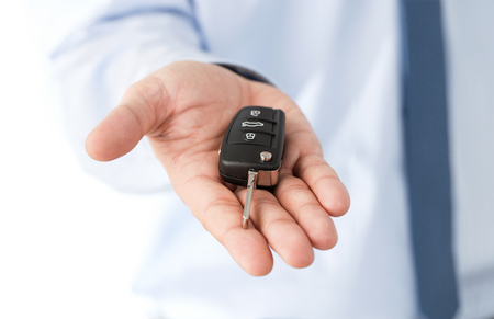 Close up of dealers hand giving a key to a dream car isolated on white background with copy space