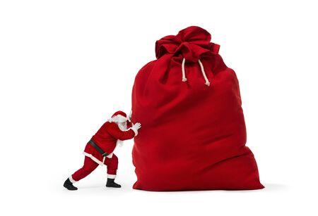 Abschluss oben von Santa Claus, die enorme Tasche von den Geschenken isiolated auf weißem Hintergrund drückt Standard-Bild