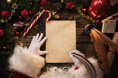 Close up of Santa Claus hands writing letter on Worden desk with copy space Stock Photo