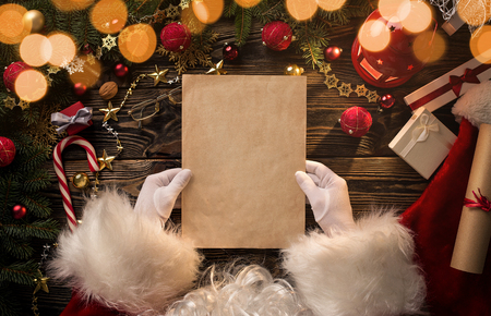 Close up of Santa Claus hands holding, reading blank letter with copy space