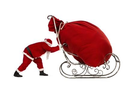 Santa Claus duwen slee met enorme zak vol met kerstcadeaus geïsoleerd op een witte achtergrond Stockfoto