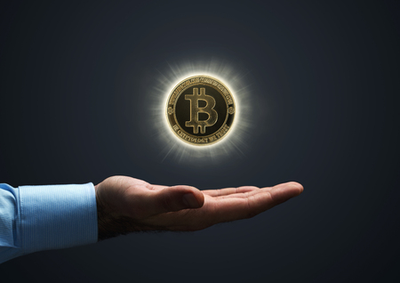 Nahaufnahme eines Geschäftsmannes , der ein virtuelles bitcoin über einem blauen Hintergrund mit Kopienraum hält