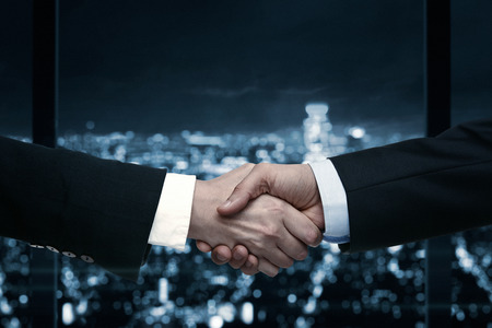 Handshake of business people with the city in the background