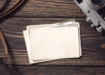 High angle view of a stack of old, blank photographs on the desk with copy