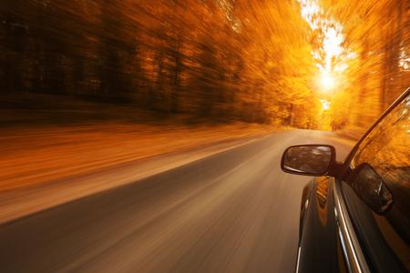 Cerca de un automóvil a exceso de velocidad en la carretera vacía, otoño con espacio de copia