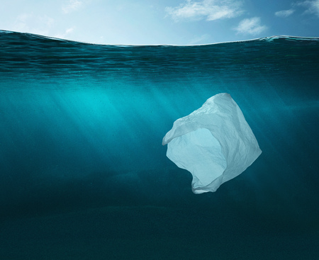 Pollution concept. Plastic bag in the ocean with copy space