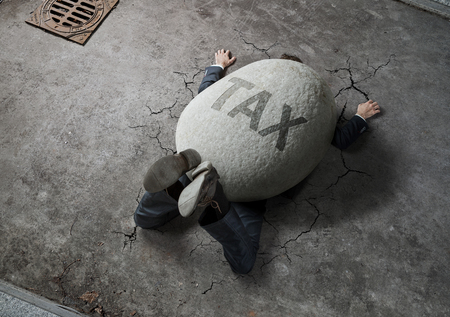 Tax concept, high angle view of businessman crushed by the huge stone on the street
