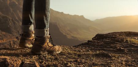Sluit omhoog van wandelaarslaarzen die van de zonsondergang in de bergen met exemplaarruimte genieten