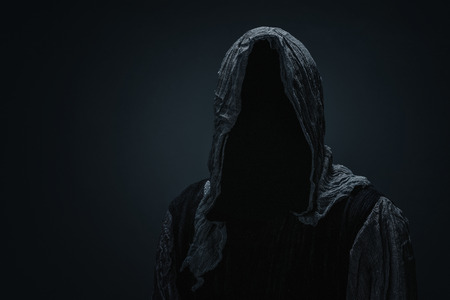 Silhouette of a Grim Reaper over dark gray background with copy space Stock Photo