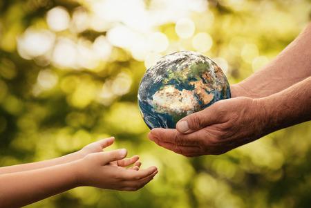 Cerca de manos de alto nivel dando pequeño planeta tierra a un niño sobre fondo verde desenfocado con espacio de copia
