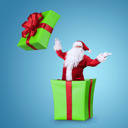 Happy Samta Claus jumping out of the christmas box isolated on blue background with copy space