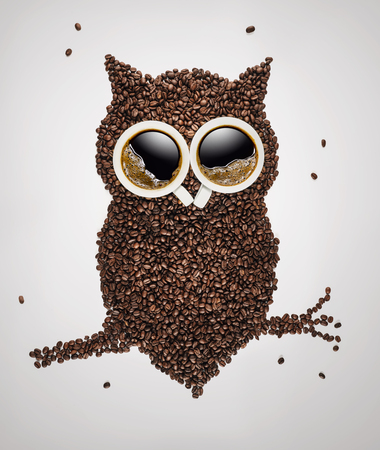 Cute owl sitting on the branch, made of coffee beans and coffee cups over light gray background with copy space