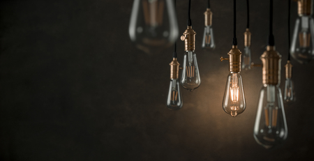 Individuality concept, one bright light bulb standing out from the crowd with copy space