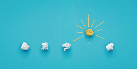 Great idea concept. Crumpled paper as a lightbulb isolated on blue background with copy space