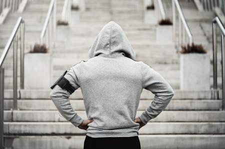 Rear view of hooded sports man about to run upstairs Stockfoto