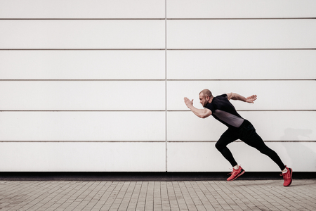 Side view of fit, sports man running by the wall with copy space