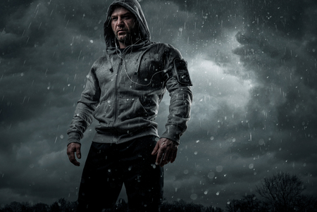 Dark, dramatic portrait of a runner standing in the rain with copy space Stockfoto