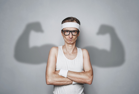 Funny sport nerd pretending tough guy isolated on white background