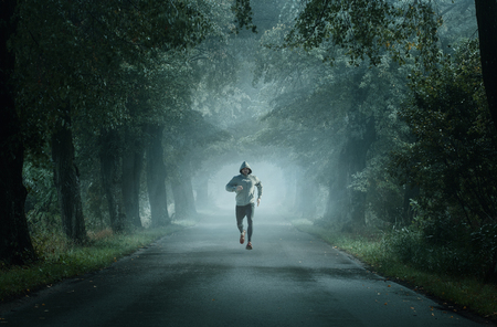 Man running on an empty road on the foggy morning with copy space
