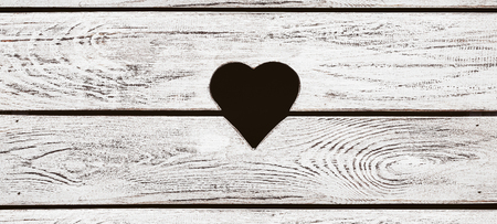 Heart shaped hole in the wooden background with copy space