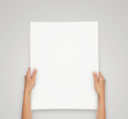 Close up of female hands holding blank paper sheet isolated on gray background with copy space