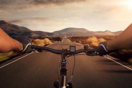 Riding a bicycle on an empty highway through the volcanic landscape with copy space Stockfoto