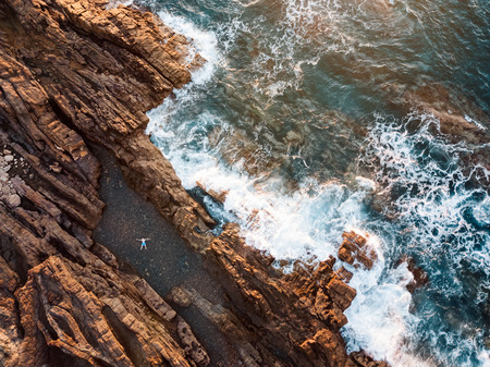 High angle view of a man relaxing in the natural swimming pool at the oceans coastline  Stockfoto