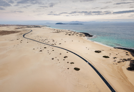 Car on the empty road, through the sand dunes, at Corralejo Natural Park before the sunset with copy space