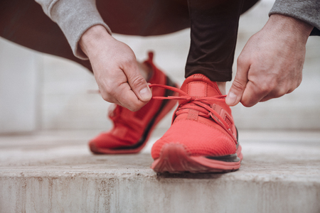 Close up of a man tying up his shoelaces before the run with copy space Stockfoto