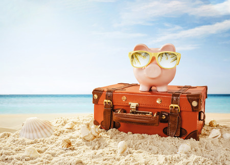 Piggy bank wearing sunglasses resting on the tropical beach with copy space Stock fotó