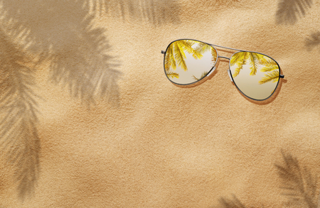 Summer concept, high angle view of sunglasses in the sand, on the beach with copy space