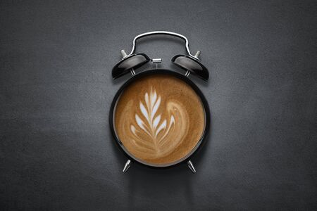 Conceptual coffee clock on dark concrete background with copy space Stock fotó