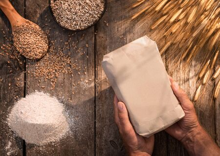 High angle view of male hands holding organic handmade eikorn flour over wooden table Stock fotó