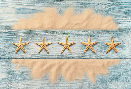 Summer holidays, five star service concept, high angle view of starfish on the wooden background Stock fotó