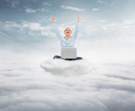 Reach the sky concept. Young succesful  businesswoman with laptop sitting on the cloud high up in the sky