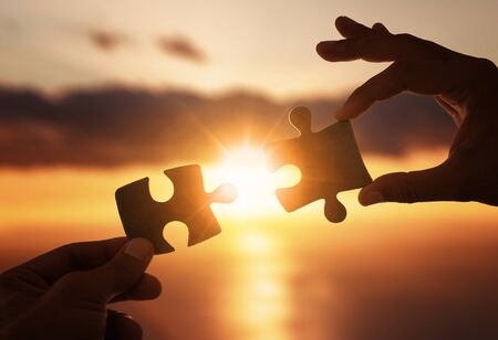 Business concept. Close up of hands connecting two pieces of jigsaw puzzle over the beautiful sunset Stock fotó