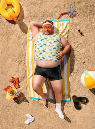 High angle view of funny overweight tourist resting on the beach 스톡 콘텐츠