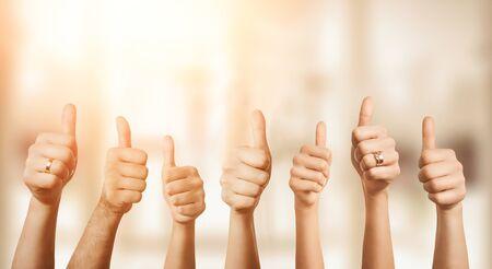 コピースペースで焦点が合っていない背景の上に親指を示す手のグループのクローズアップ