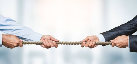 Tug of war, two businessman pulling a rope in opposite directions over defocused background with copy space Stockfoto