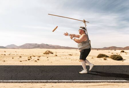 Funny overweight man chasing the hot dog on the stick through the empty road with copy space